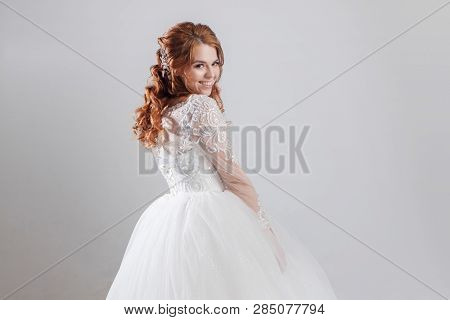 Happy young woman bride in a lavish wedding dress. Light background. poster