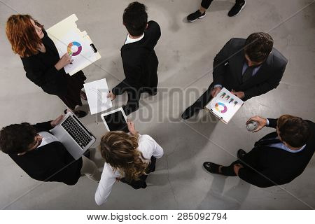 Team Of Business Person Works Together On Company Statistics. Shooted From Above. Concept Of Teamwor