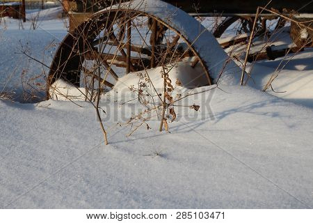 poster of iron old rusty wheel cart stuck in the snow cart