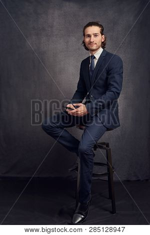 Handsome Young Man With Long Hair, Wearing Stylish Suit And Blue Tie, Holding Smartphone In His Hand