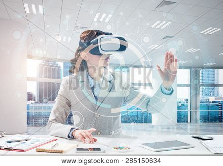 Horizontal Shot Of Beautiful And Young Business Woman In Suit Using Virtual Reality Headset With Dig