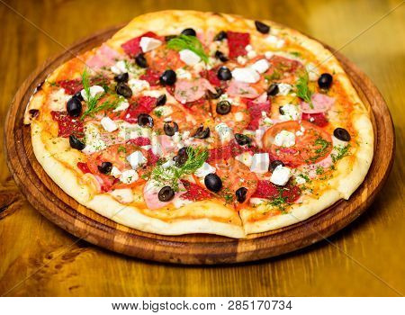 Pizza Served With Dill. Pizza With Tomatoes Black Olives And Ham. Take Away Food Concept. Pizzeria R