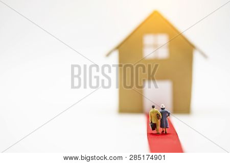 Behind Miniature Man And Woman Model Hand Carry Suitcase And Walk Through Coins Stacking For Move To