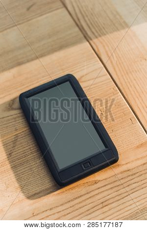Ebook With Blank Screen Lying On Wooden Table