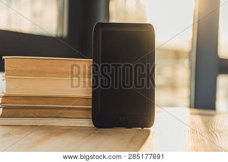Ebook With Blank Screen Near Paper Books On Wooden Table