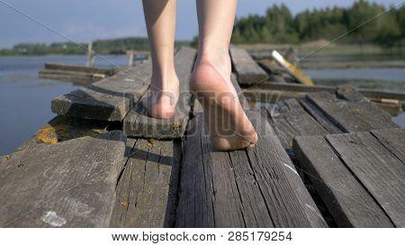 Boy Bare Feet Walking Along The Old Decrepit Pier