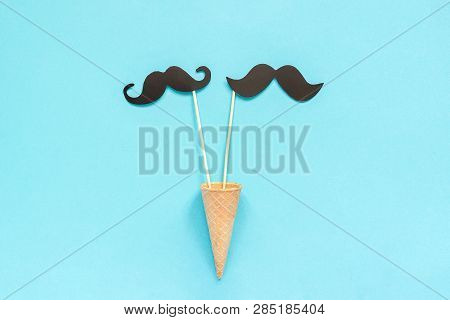Couple Paper Mustache Props On Stick In Ice Cream Waffle Cone On Blue Background. Concept Homosexual