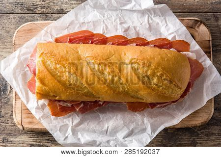 Spanish serrano ham sandwich on wooden table. Top view. poster