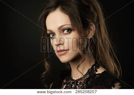 Pretty Woman Face Over Black Studio Background