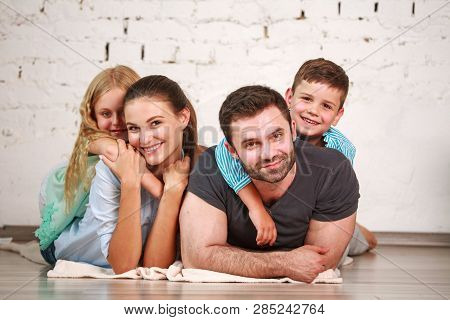 Happy Dreamy Young Couple Of Parents With Two Children At Home Having Fun Together