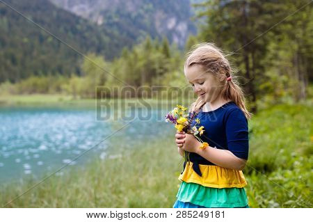 Child Hiking In The Alps Mountains Looking At Beautiful Lake. Kid In Alpine Flower Field At Snow Cov