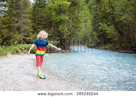 Children Hiking In The Alps Mountains Crossing River. Kids Play In Water At Mountain In Austria. Spr