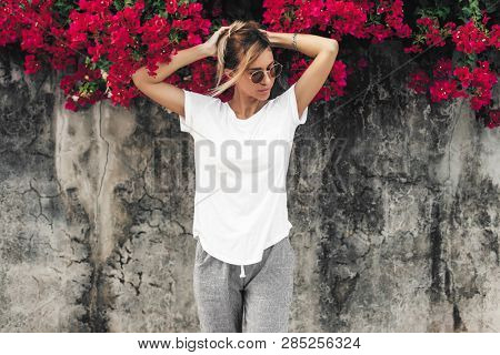 Hipster girl wearing blank white t-shirt posing against gray street wall with spring flowers, blank mockup for tshirt print store