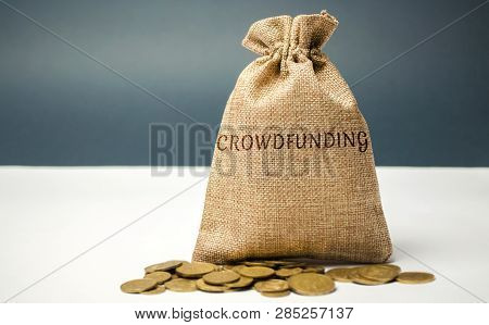 Money Bag With Coins With The Word Crowdfunding. Voluntary Association Of Money Or Resources Via The