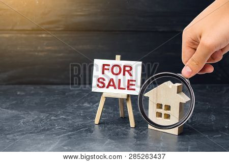 Magnifying Glass Is Looking At The Wooden House Stand With A Sign For Sale. Selling A House Or Apart
