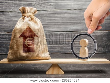 Magnifying Glass Is Looking At A Man Figurine And Euro Money Bag With Arrow Up On Scales. Average Sa