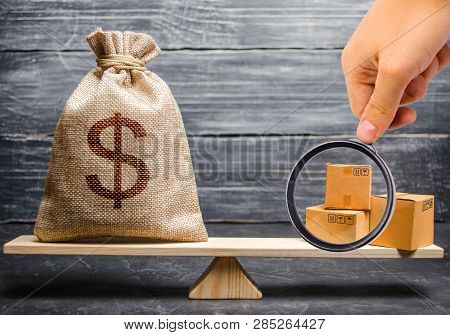 Magnifying Glass Is Looking At The Bunch Of Boxes. Bag Of Money On The Scales. Conceptual Trade Bala
