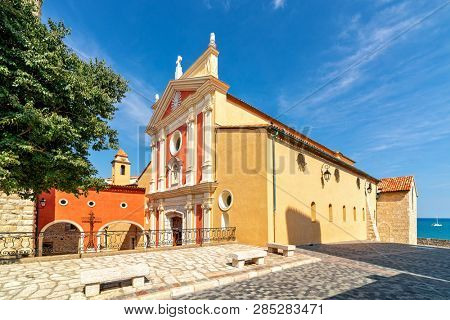 View of Antibes Cathedral on small town square under beautiful blue sky as Mediterranean sea on background in Antibes, France.