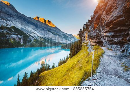Idyllic view of the azure lake Oeschinensee. Location place Swiss alps, Kandersteg, Bernese Oberland, Switzerland, Europe. Scenic image of popular tourist attraction. Discover the beauty of earth.
