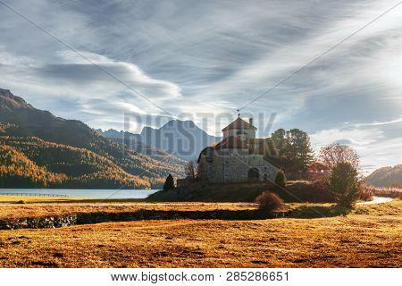 Amazing autumn sunny day at Champferersee lake in the Swiss Alps. Castle of Crap da Sass, Silvaplana village, Switzerland, Europe