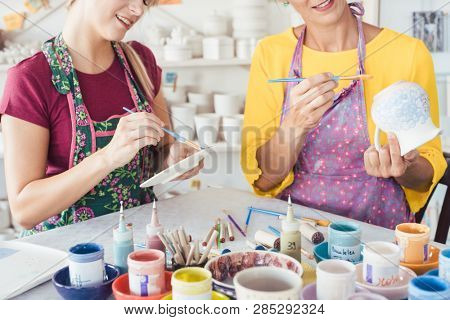 Two women painting own ceramic tableware in DIY workshop with brushes