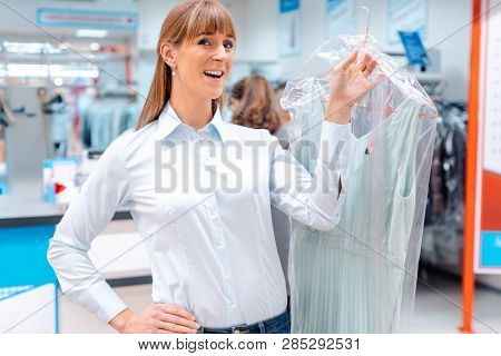 Satisfied woman customer getting clean clothes back from the textile cleaning
