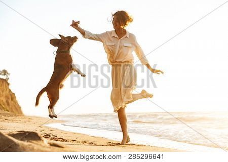 Image of happy woman 20s playing with her dog while walking by seaside