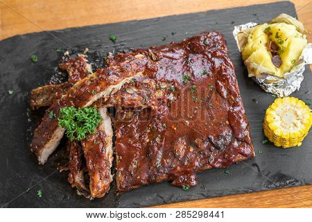 Grilled Barbecued Pork Baby Back Ribs with baked potato and grilled sweet corn