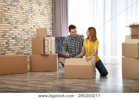 Couple Unpacking Cardboard Box In Their New House. Moving Day