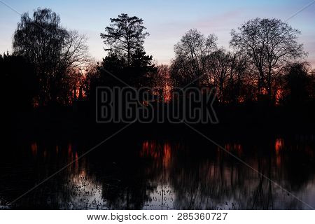 Dark And Moody Sunset Over Lake Or Pond With Silhouette Of Bare Trees