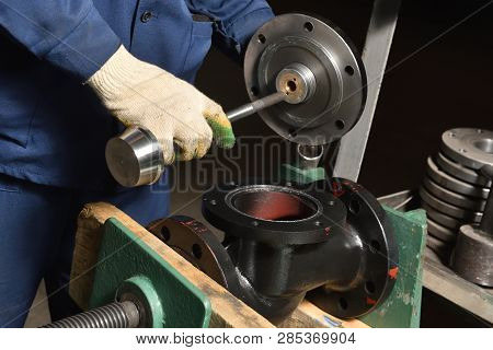 The base for the valve is installed and clamped in a vice for assembly at the factory and the worker installs and fastens the components. poster