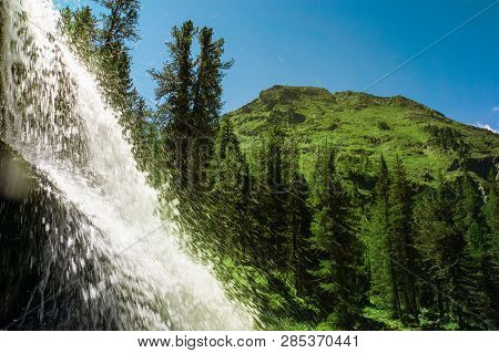 Beautiful Torrent Of Waterfall. Water Falling On The Falls. On The Background Of Beautiful Mountains