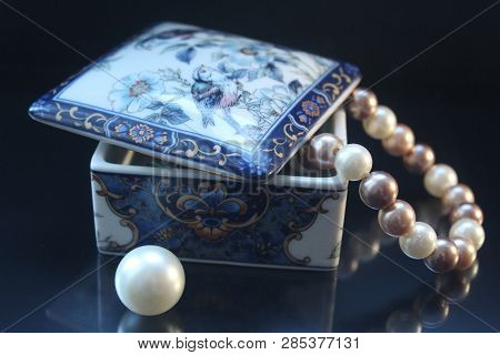 The Beautiful Beads From Pearls Which Is Dangling Down From A Ceramic Casket, Nearby A Big Bead. Jew