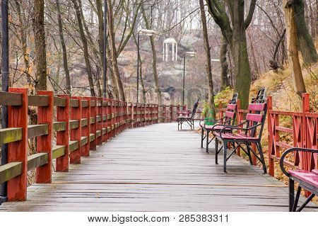 Wooden Path - Hinged Bridge With Wet Boards, Wrought Iron Benches And Lanterns In The Park On A Hill