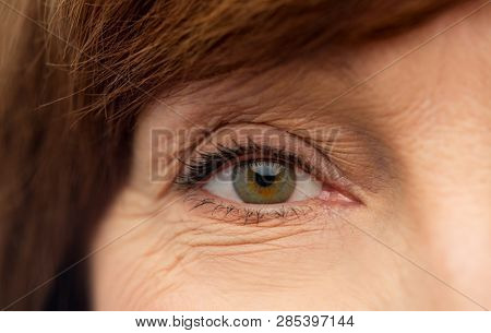 beauty, vision and old people concept - eye of senior woman