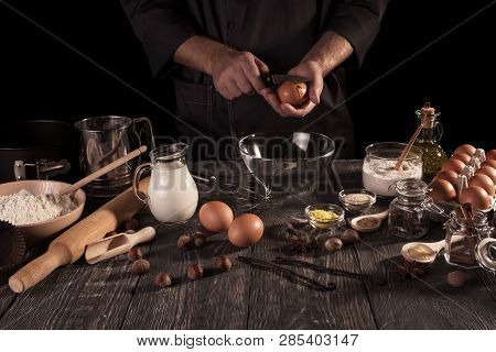 Male Chef Prepares Fragrant Vanilla Cake With Lots Of Spices. Dark Key