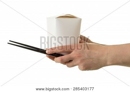 Chinese Noodles Wok In A Cardboard Box In Hand Holding Chopsticks Isolated On White Background