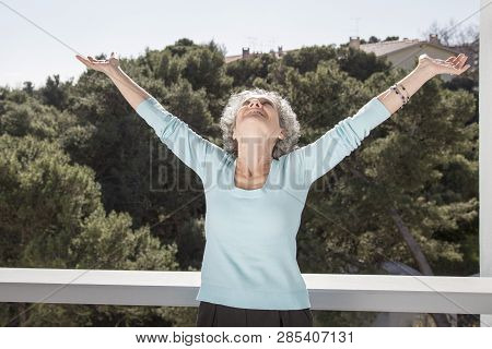 Portrait Of Happy Senior Woman Standing With Raised Arms On Balcony. Positive Retired Woman Enjoying