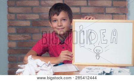 Portrait Little Boy Showing Whiteboard With Handwriting Idea. Child Is Lost In Thought. Preadolescen
