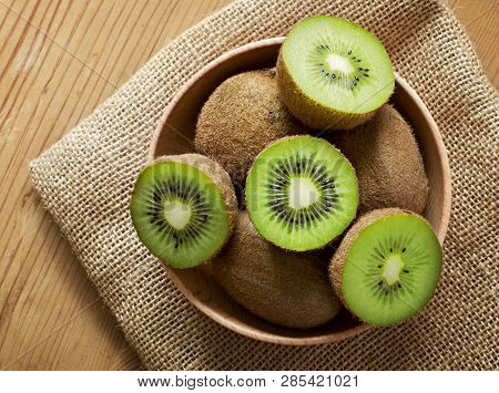Delicious Ripe Kiwi Fruits In A Wooden Bowl. Top View Scene, Healthy Eating Or Healthy Lifestyle. Cr