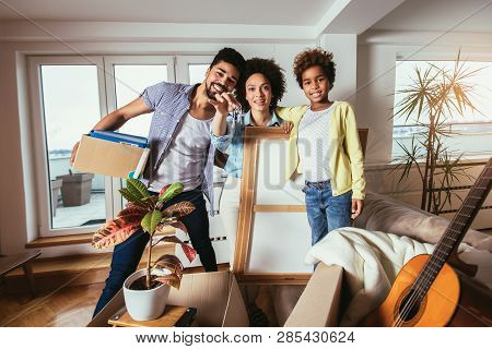 African American Family, Parents And Daughter, Unpacking Boxes And Moving Into A New Home, Having Fu