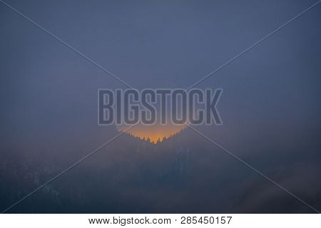 Last Minutes Of Sunset Behind The Forest On A Very Foggy Evening On A Winterday In Styria, Austria