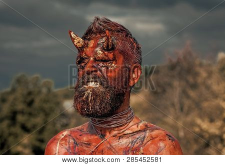 Halloween dragon creature on natural environment. Temptation, hell, evil, horror, darkness concept. Satan with red blood and wounds on face skin. Demon man with beard. Devil head with bloody horns poster