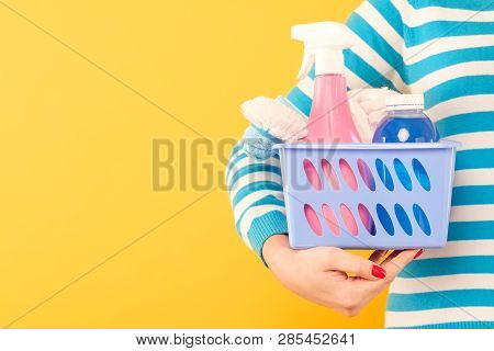 Home Cleaning Products. Housekeeping Concept. Woman Holding Basket With Cleanup Supplies. Copy Space
