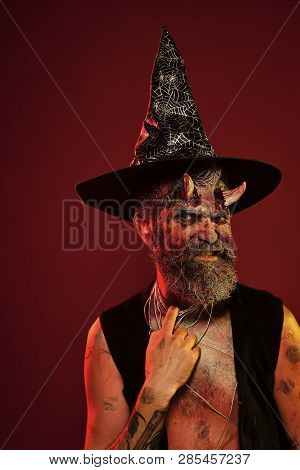 Halloween Man With Satan Horns In Witch Hat On Head. Devil Hipster With Beard, Blood, Wounds On Face