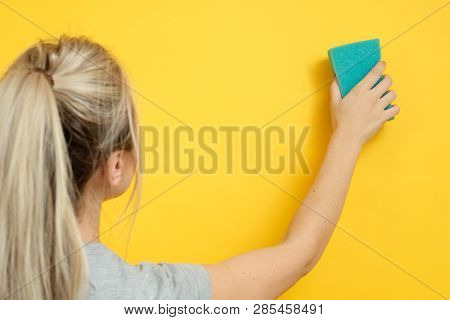 Organized home cleanup. Spotless cleaning. Woman with sponge wiping imaginary spot. poster