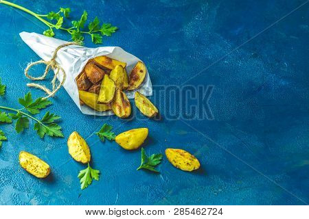 Baked Potato Wedges On Paper With Addition Sea Salt And Parsley On A Dark Blue Concrete Background