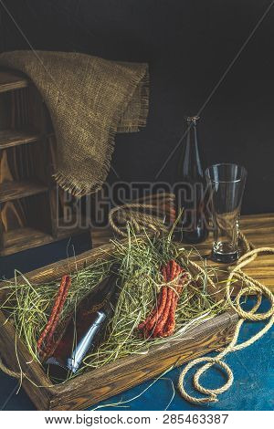 Craft Beer With Sausages Kabanosi In The Wooden Box Above Fresh Hay Or Dried Grass Beside Beer Bottl