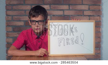 Portrait Little Boy Showing Whiteboard With Handwriting Word You Are Fired. Child With Spectacles On