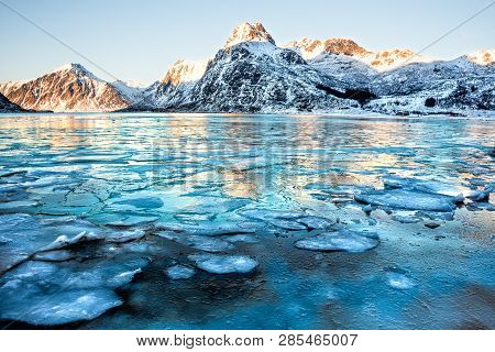 Landscape From Lofoten, Norway With Mountains Reflected In The Water Full Of Ice Cubes